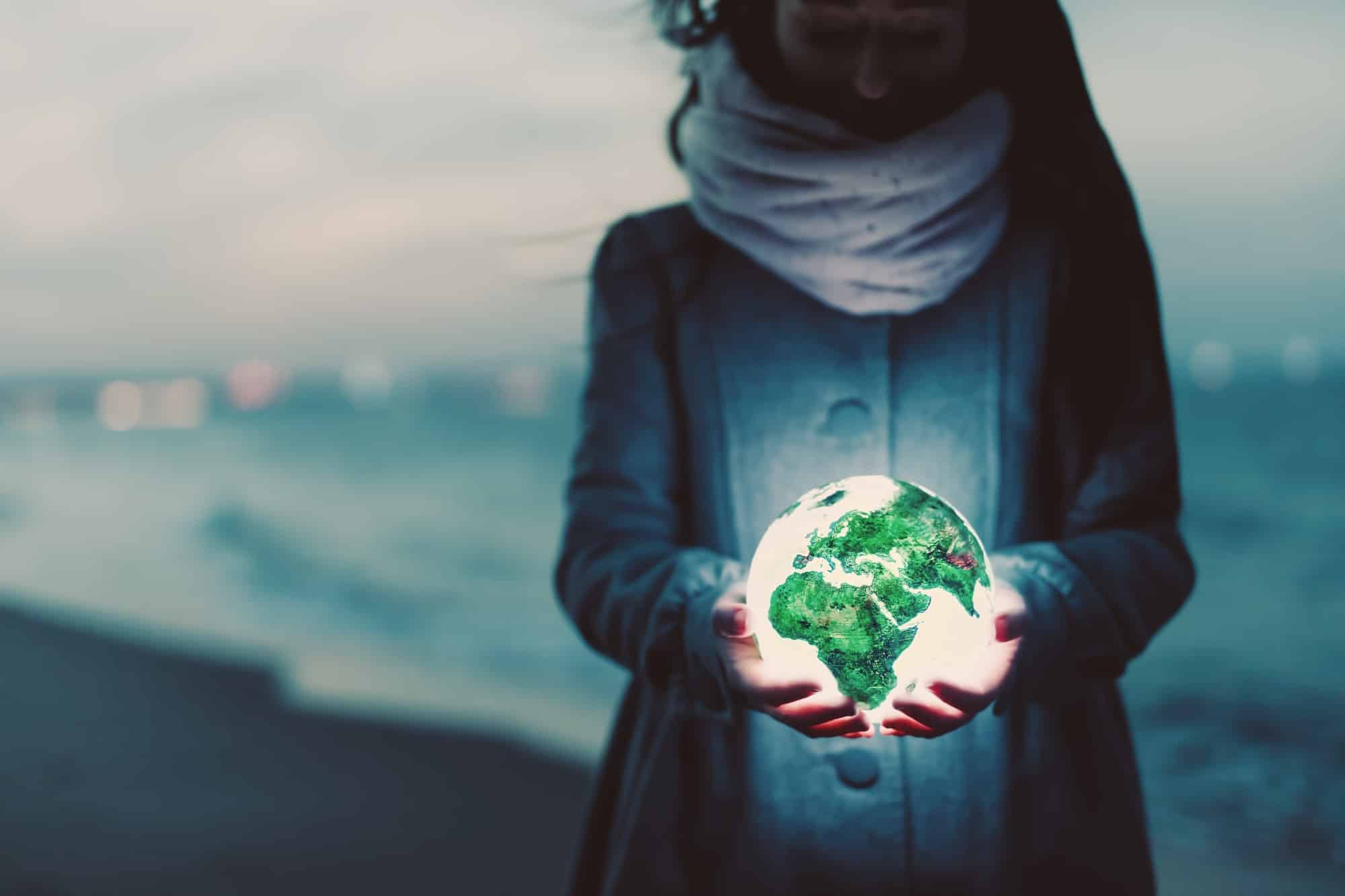 Woman holding a bright globe in her hands